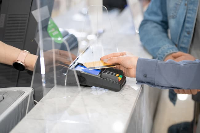 An image of a man making a purchase with a credit card.